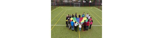 Children holding a round, rainbow blanket on a field